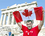 Nicolas Gill poses with the Canadian flag in front of the Parthenon in Athens, Gill carried the flag to lead the Canadian team at the Olympic games opening ceremonies.
