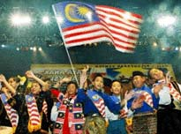Wearing traditional costumes, Malaysian schoolchildren sing patriotic songs and wave a national flag during a campaign entitled 'We Are The Children Of Malaysia' in Kuala Lumpur March 2, 2004, a patriotic campaign to inspire unity,  and to foster integrity and national pride among schoolchildren. REUTERS/Bazuki Muhammad